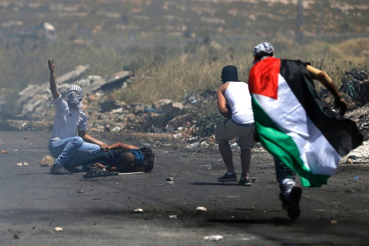 Palestinian protesters run to help a fellow demonstrator after he was injured during clashes with Israeli security forces following a protest marking the 69th anniversary of Nakba, which remember those displaced at the time of the 1948 founding of Israel, near the Jewish settlement of Beit El, near the West Bank city of Ramallah on May 15, 2017. / AFP / ABBAS MOMANI