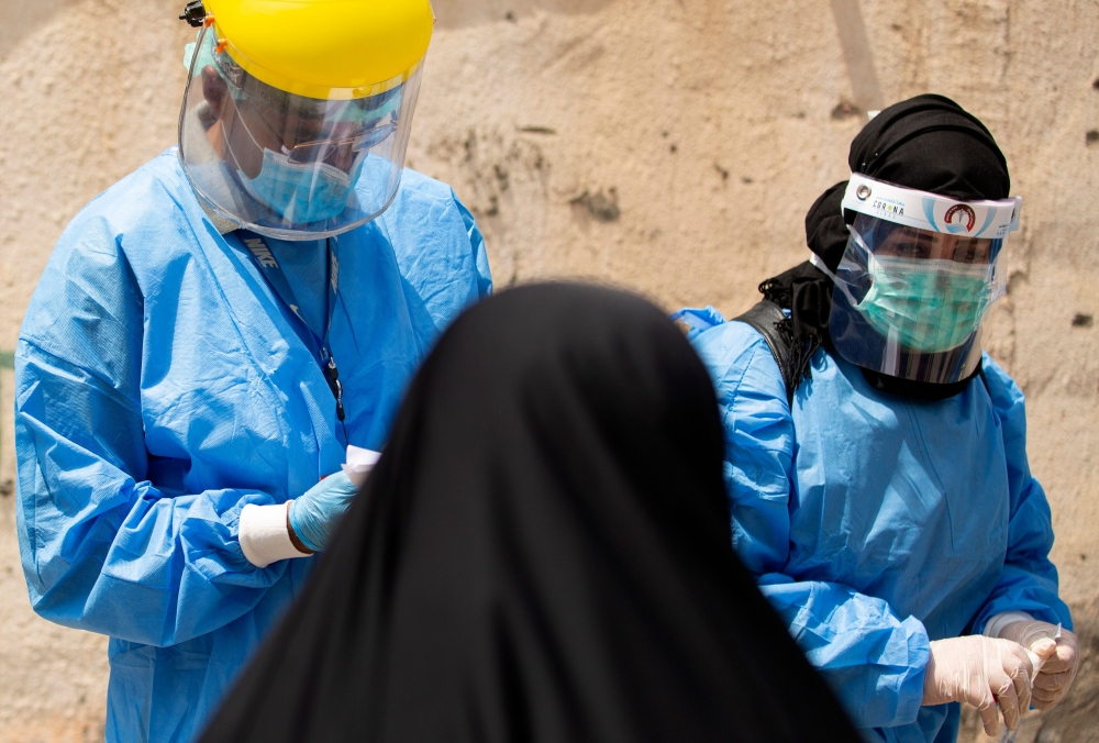 Medical workers dressed in PPE (personal protective equipment) prepare to take swabs from subjects being tested for COVID-19 coronavirus disease, in the 5-Miles district of Iraq's southern Basra on June 2, 2020. (Photo by Hussein FALEH / AFP)