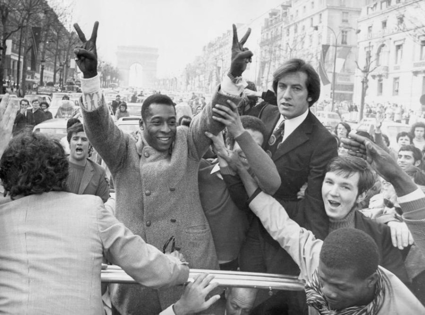 FILE - In this March 30, 1971 file photo, Brazil's soccer player Pele flashes victory signs as he rides down the Champs Elysees on his way to a reception at the Town Hall in Paris, France. On Oct. 23, 2020, the three-time World Cup winner Pelé turns 80 without a proper celebration amid the COVID-19 pandemic as he quarantines in his mansion in the beachfront city of Guarujá, where he has lived since the start of the pandemic. (AP Photo/Jean-Jacques Levy, File)