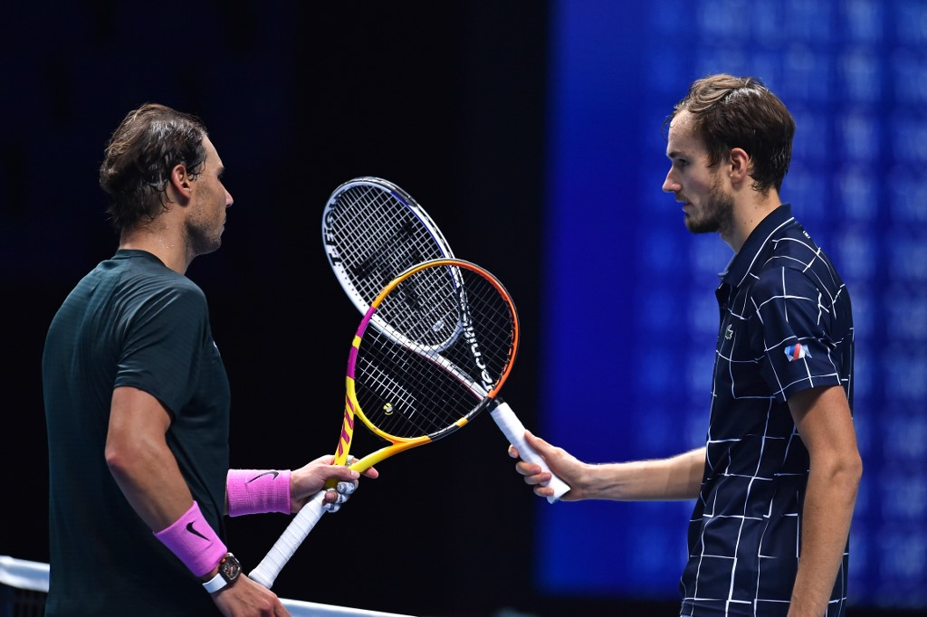 Russia's Daniil Medvedev (R) gestures to Spain's Rafael Nadal (L) after winning their men's singles semi-final match on day seven of the ATP World Tour Finals tennis tournament at the O2 Arena in London on November 21, 2020. - Medvedev won the match 3-6, 7-6, 6-3. (Photo by Glyn KIRK / AFP)
